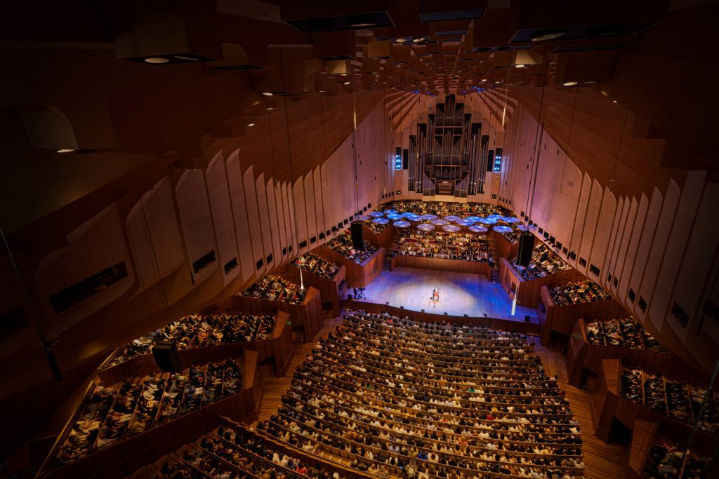 The interior of the Sydney Opera House taken from above. Cellist Yo-Yo Ma is at the center of the stage, with a white and blue spotlight on him.